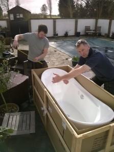 Tony and Carl unpacking a large white bath